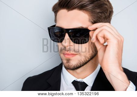Portrait Of Handsome Confident Man Touching His Glasses