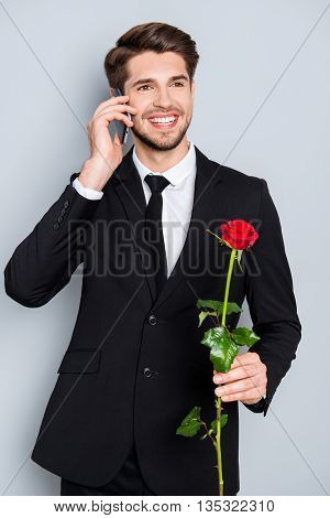 Young Happy Man With Rose Talking On Phone With His Girlfriend