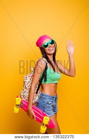 Photo Of Attractive Funny Young Woman With Backpack Holding Pink Longboard Smiling