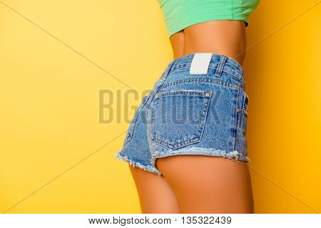 Close Up Photo Of Beautiful Girl's Buttocks  Wearing Jeans On  Yellow Background