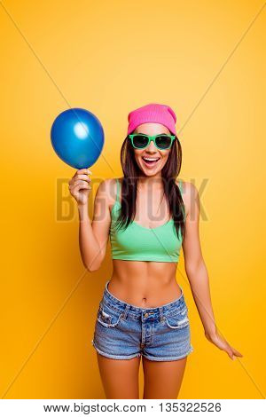Cheerful Excited Hipster Girl In Pink Hat  Holding Balloon On Yellow Wall