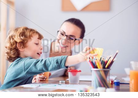 So nice. Excited little boy trying to make soap bubbles while sitting with his magnificent mother at the table