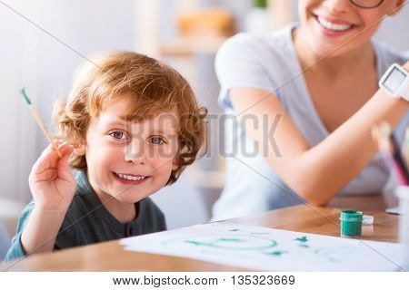 So exciting. Cheerful little smiling boy holding a brush and looking at the camera while painting with his mother