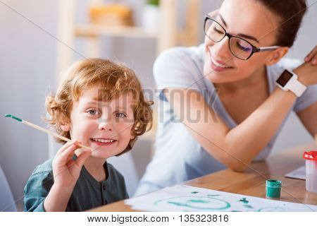 Little painter. Sincere little smiling boy holding a brush for painting and looking at the camera while his mother looking at him