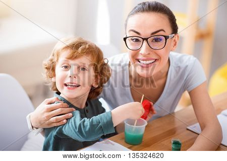 We are happy. Little charming boy washing a brush and his beautiful mother hugging him while looking at the camera and smiling