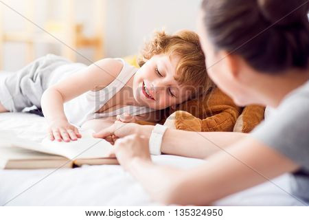 I need some sleep. Adorable little tired boy lying on the bed and touching hands of his mother