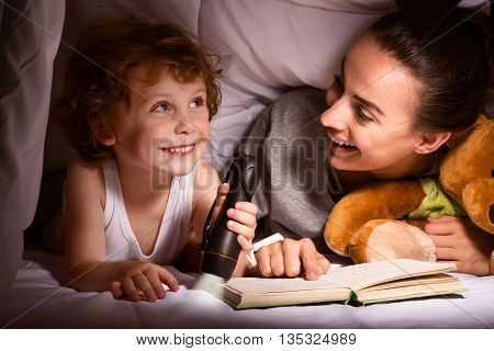 Our kingdom. Cheerful young mother and cute child with flashlight reading a book under the blanket