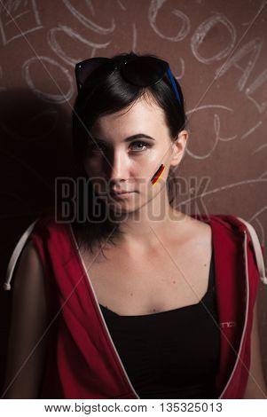 cute girl is fan of the German national team brunette paint a German flag on my cheek
