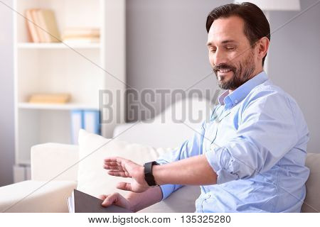 What time is it. Smiling middle-aged man looking at his smartwatch while sitting on the sofa with a book