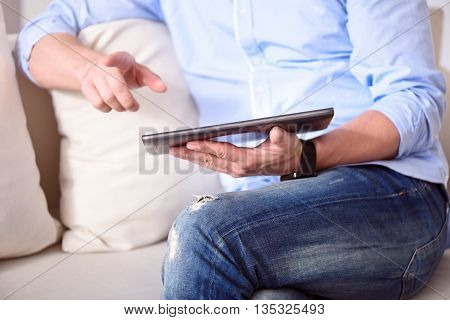 What is new here. Picture of hands of man using a tablet while sitting on the sofa