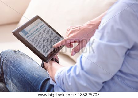 Lets read some news. Picture of hands of man holding a tablet with news on the screen while he sitting on the sofa