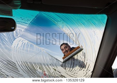 Adult man washing dirty windshield of his car.