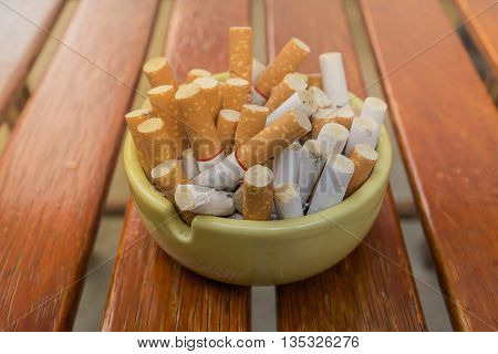 cigarette stub in dirty ashtray on wood table