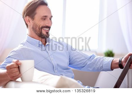 Happy day. Bearded cheerful mature man looking at the tablet while drinking coffee and sitting on the sofa