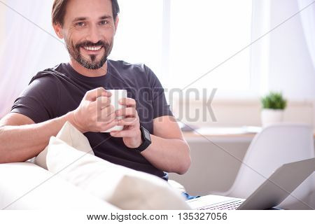 At last I am at home. Smiling mature bearded man looking at the camera while sitting and holding a cup