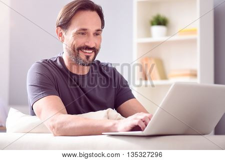So easy to be in touch. Pleasant good looking mature man looking at the screen of his laptop while sitting on the couch