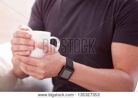 I need some coffee. Close up of hands of a man holding a cup with both hands and wearing smartwatch