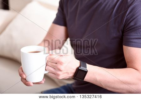 Drink it. Close up of hands of a man holding a cup of tea while sitting on the sofa and wearing a smart watch