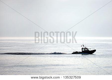 Motor boat backlit in early morning sun