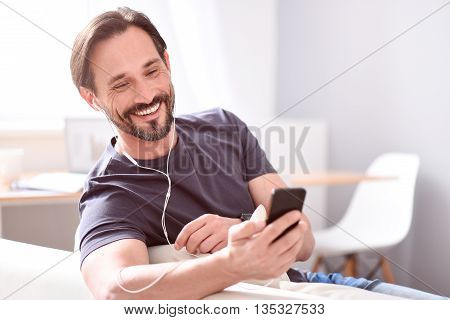 The way to be in touch. Cheerful handsome bearded man using earphones and looking at his phone