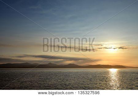 Sunset over calm sea wth mountains sky