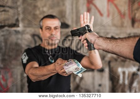 Robber With A Gun Taking Money From Victim