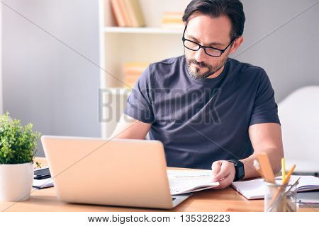 Analyzing the situation. Serious mature bearded man with glasses looking at newspaper while sitting in front of the laptop at the table