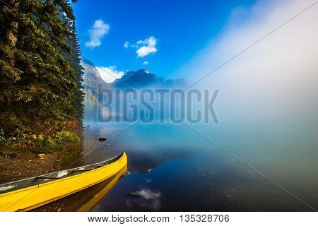 Misty autumn morning in the mountain Emerald Lake. Fishing boats moored on the shore. Canada, Yoho National Park