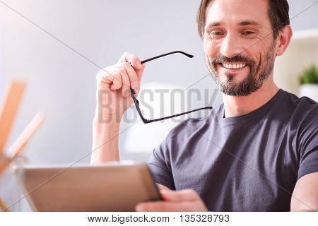 I am so happy. Joyful bearded middle aged man smiling sincerely and holding glasses while sitting and looking at the tablet in his hands