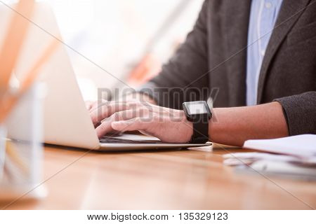 Mind the deadline. Picture of hands of man tapping on the laptop while he sitting at the table with a smartwatch on his hand