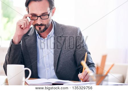 Looking for a new strategy. Thoughtful serious man touching his glasses while sitting at the table thinking about his work project