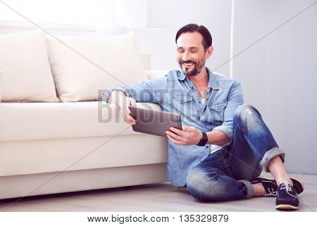 In such a good mood. Joyful mature relaxed man smiling and using a tablet while sitting on the floor near a couch