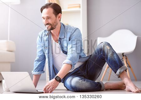 Feel yourself comfortable. Delighted mature man smiling while sitting on the floor and using his laptop