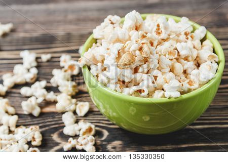 Sweet Caramel Popcorn in Green Bowl on Wooden Background, Selective Focus, Unhealthy Food Concept