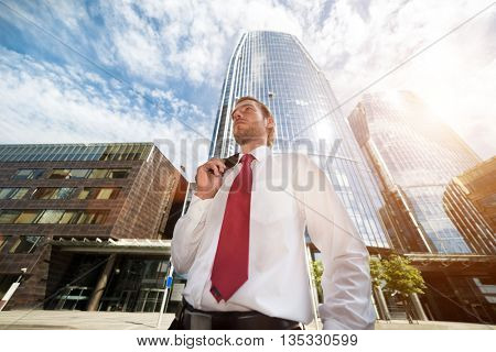 Businessman in front of a skyscraper. Controlled flare effect