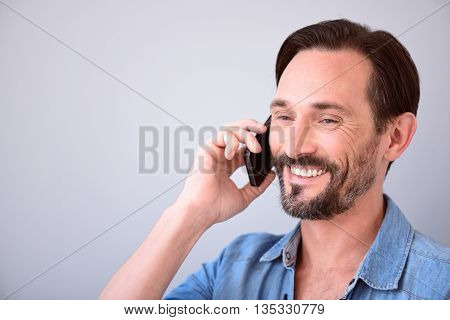 Call me. Close up of a delighted middle-aged bearded man talking on the phone on the grey background