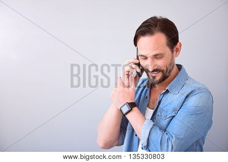 Glad to hear you. Cheerful bearded happy man talking on the mobile phone while standing on the grey background