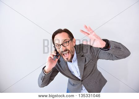 I am furious. Candent bearded mature boss talking on the phone and screaming on his collocutor isolated on grey background