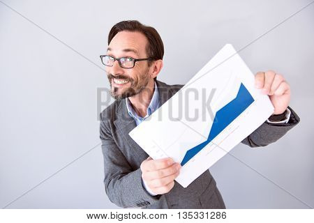 It is a progress. Extremely happy bearded professional holding a board with a graph while standing isolated on the grey background