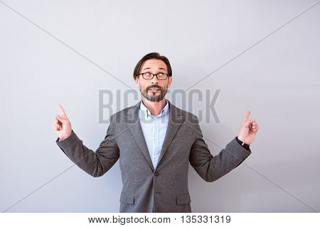I will show you. Bearded confident mature man looking up and pointing with hands while talking and standing isolated on the grey background
