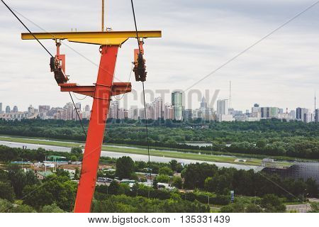 rusty old red yellow ski lift against the backdrop of the Moscow city. With copyspace.