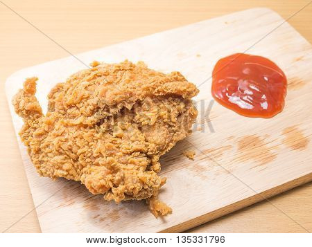 fried chicken on a chopping broad with a tomato sause set on a wood background