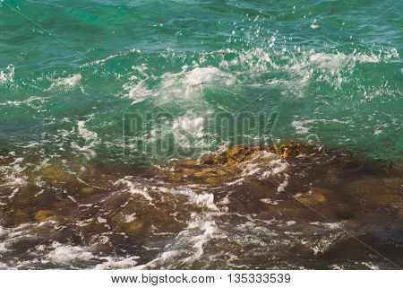 Photo closeup of beautiful clear turquoise sea ocean water surface with ripples and bright splash on seascape background, horizontal picture.