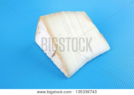 light swiss gauda cheese on blue board