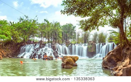 Dong Nai, Vietnam - March 1st, 2015: Giang Dien Waterfall inside the old trees with white water stream flowing like silk sheet to attract tourists to bath, relaxation on a weekend in the area of ecotourism in Dong Nai, Vietnam