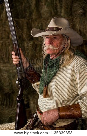 Authentic old west cowboy with shotgun, hat and bandanna in stable