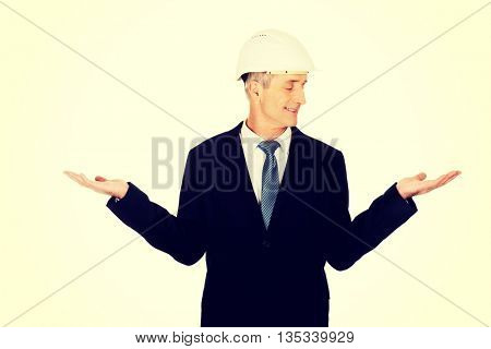 Businessman with hard hat holding copyspace