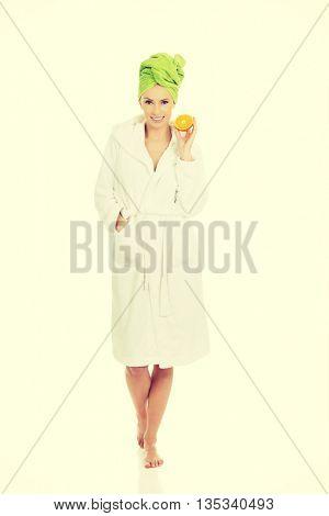 Spa woman in bathrobe holding orange.