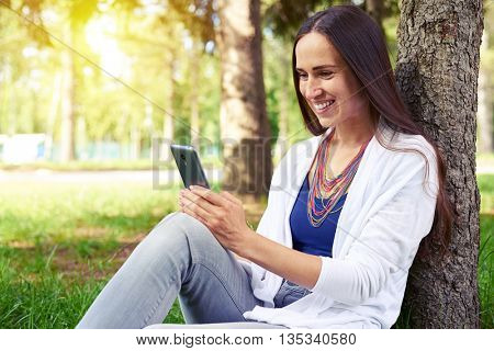 Smiling charming lady is sitting under tree in sunlit park and watching something on her smart phone