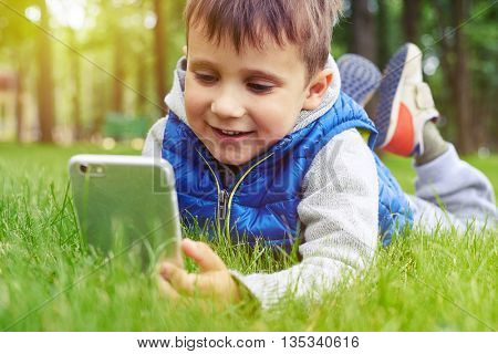 Little boy with smart phone is resting on green grass in park on a sunny warm day